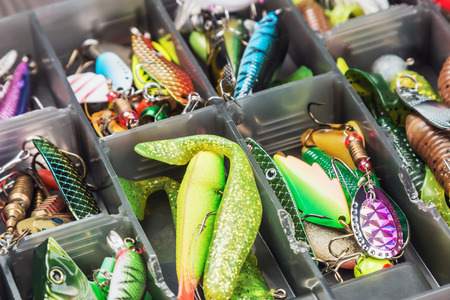 fishing lures and accessories in the box background. Focus in the center of the bait Archivio Fotografico
