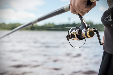 fishing lake: hand holding a fishing rod with reel. Focus on Fishing Reels