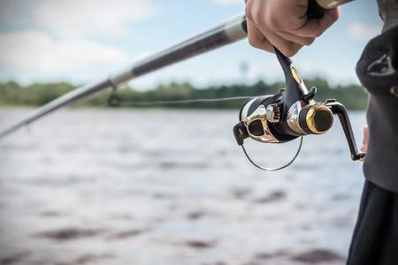 pescando: mano que sostiene una ca�a de pescar con carrete. Enfoque en los carretes de pesca