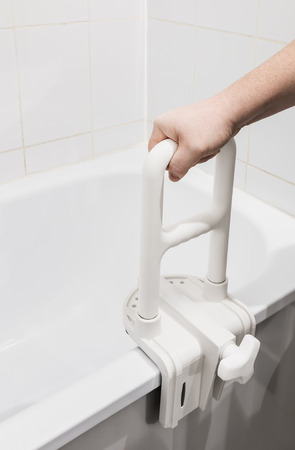 handrail: hand holding the handrail in the bathroom. Focus on the handrail Stock Photo