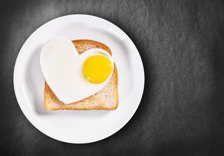 hartvormige gebakken eieren en gebakken toast op een zwarte achtergrond.