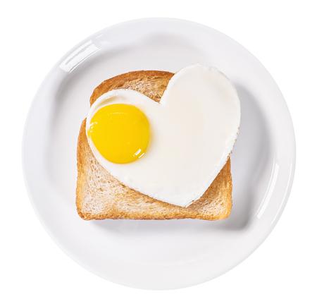 desayuno romantico: huevos fritos en forma de coraz�n y tostadas frito aislado en un fondo blanco Foto de archivo