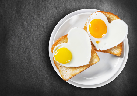 Two heart-shaped fried eggs and fried toast on a black background Foto de archivo