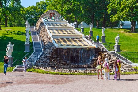 peterhof: ST PETERSBURG, RUSSIA - JUNE 21, 2015: Tourists in Peterhof fountain Cascade Chess Mountain, The Peterhof Palace Editorial