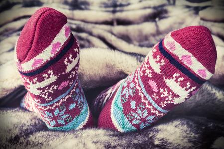Piernas femeninas en los calcetines de Navidad bajo un manto de pieles. imagen tonificación Foto de archivo - 44715360