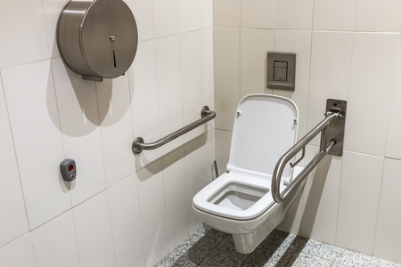 a toilet seat: toilet with handrails for the disabled Stock Photo