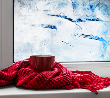 red cup with hot drink on the background of frozen window 免版税图像