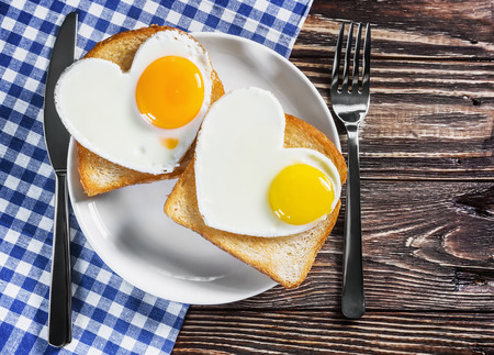 cholesterol: Two toast with scrambled eggs in the shape of a heart on a plate