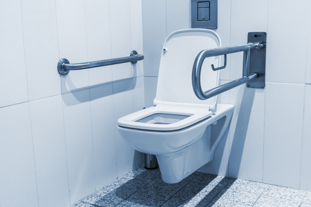 cubicle: Public toilet cubicle for the disabled. Focus on the toilet, shallow depth of field Stock Photo