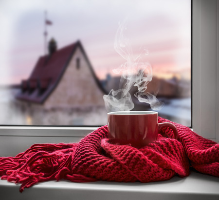 cold drinks: cup with a hot drink on the windowsill in the background of a winter city. Focus on the edge of the cup