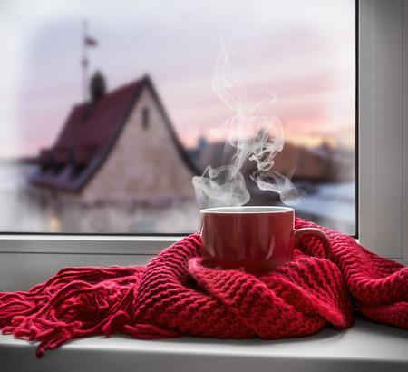 bebidas frias: taza con una bebida caliente en el alféizar de la ventana en el fondo de una ciudad de invierno. Enfoque en el borde de la copa