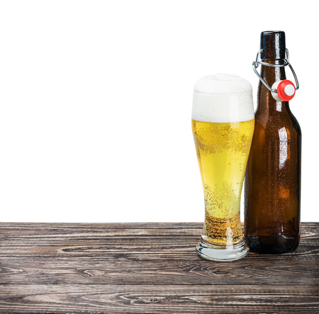 beer bottle: glass of beer and an empty bottle on the table isolated on white background