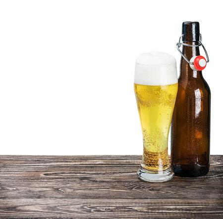 bebidas alcohÓlicas: vaso de cerveza y una botella vacía en la mesa aislada en el fondo blanco Foto de archivo