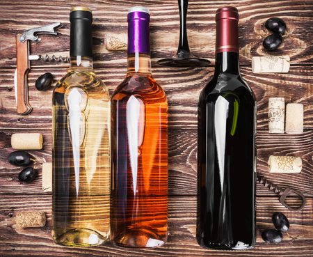 bottle opener: bottles of wine and various accessories on wooden table