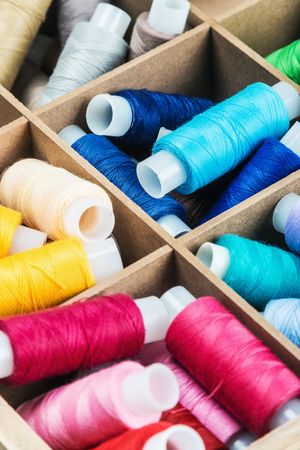 sewing cotton: Multicolor sewing threads in a wooden box. focus on strings in the center of the frame