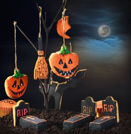 Halloween cookies hanging on a tree in the night sky. Focus on the graves on the ground Stock Photo