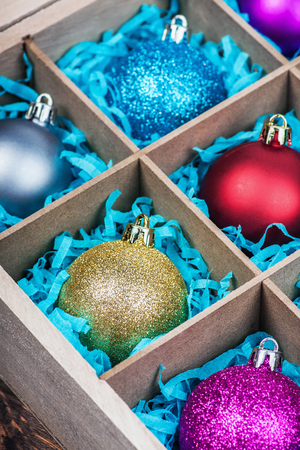 christmas tree ball: Christmas-tree balls in a wooden box. Focus on a gold Christmas tree ball Stock Photo