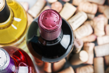 vins: Wine and corks isolated on white background. Focus on the neck of the bottle