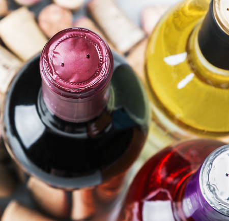 des vins: Wine and corks isolated on white background. Focus on the neck of the bottle