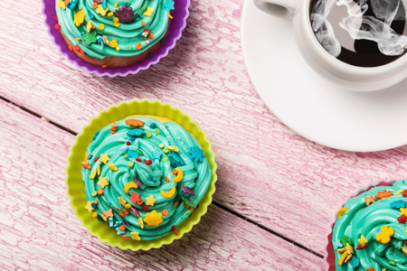 cupcakes: Fresh cupcakes and coffee on the wooden table Stock Photo
