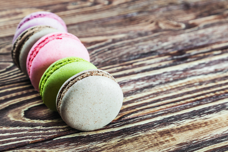 focus on the foreground: different colors macaron on a wooden table. focus foreground Stock Photo