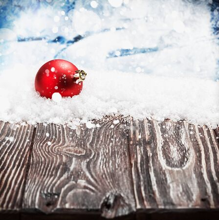 christmas balls: Christmas ball on a wooden table in the snow. focus on Christmas ball
