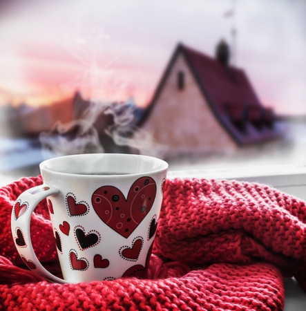 cup with a hot drink on the windowsill in the background of a winter city. To use the greeting for Valentines Day Stock Photo