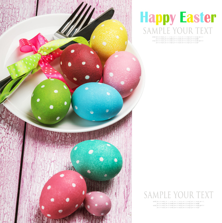 pascha: colored Easter eggs on wooden background. focus on the plate with eggs