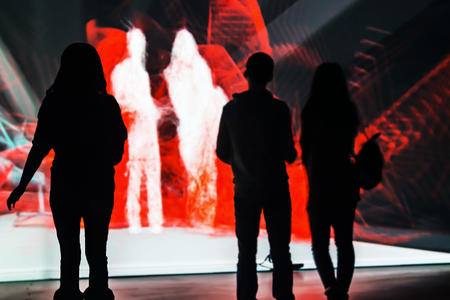 affecting: Moscow, Russia - January 28, 2016: people standing in front of an interactive installation in the exhibition center Mars. Focus on the silhouette of a man on the left