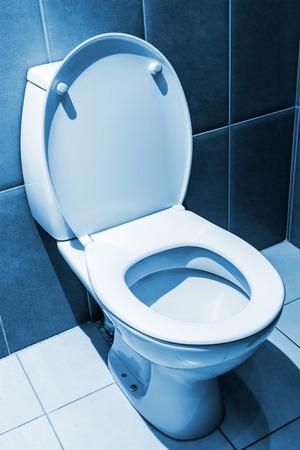 white ceramic toilet in tiled bathroom. Focus on the edge of the toilet bowl. toned image