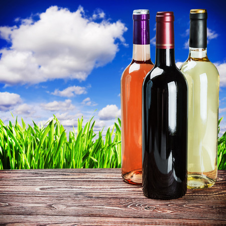 fining: bottles of wine of different sort on the wooden table Stock Photo