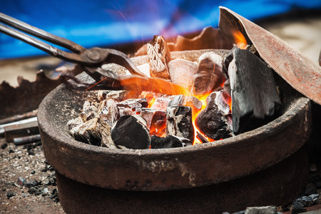 forge a burning forge and tools. focus on the coals and sparks Stock Photo