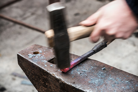 workpiece: Making decorative element in the smithy on the anvil. focus on a metal workpiece Stock Photo