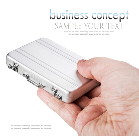 disclose: hand holds a small aluminum case isolated on white background. Focus on the handle of the case. for example the text, can be easily removed
