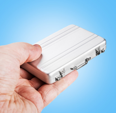 disclose: hand holds a small aluminum case. Focus on the locks of the case, soft focus