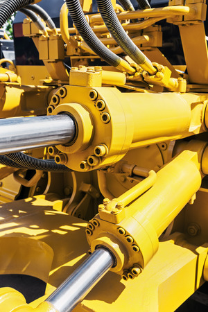 hydraulics: hydraulics tractor yellow. focus on the hydraulic pipes Stock Photo