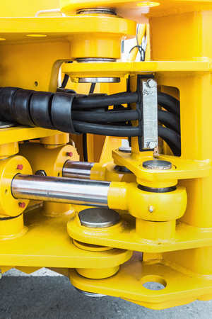 hydraulics tractor yellow. focus on the hydraulic pipes Stock Photo