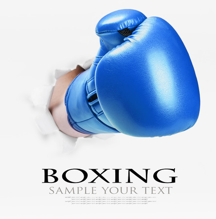 deleted: hand in boxing glove broke through the white paper wall. text deleted Stock Photo