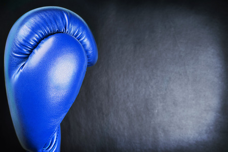 bout: blue leather boxing gloves on a black background