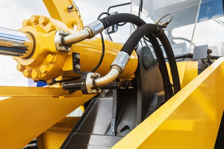 idraulico trattore giallo. concentrarsi sui tubi idraulici Archivio Fotografico