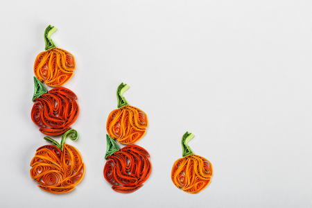 Pumpkins in quilling techniques for Halloween on a light background Stock Photo