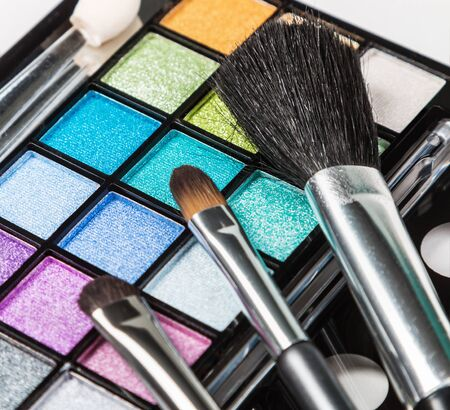 eyemakeup: Make-up colorful eyeshadow palettes with makeup brushes. Focus on the black makeup brushes. Shallow depth of field Stock Photo