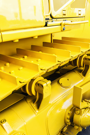 metal tracks on the tractor. yellow tracks tractor. Focus on tractor tracks Stock Photo