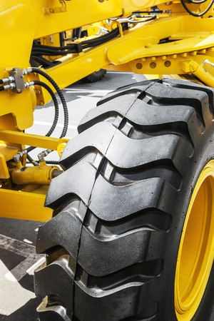big wheel: yellow tractor with a big wheel. Wheel with a large tread. focus on the big wheel