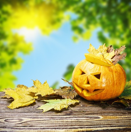 Jack Lantern for Halloween on wooden table on a background of nature Stock Photo
