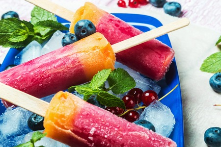 popsicles: popsicles with red currants and blueberries on a wooden table. sorbet
