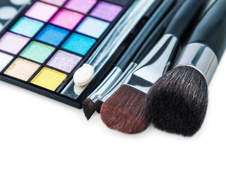 eyemakeup: Make-up colorful eyeshadow palettes with makeup brushes. Focus on the makeup brushes. Shallow depth of field