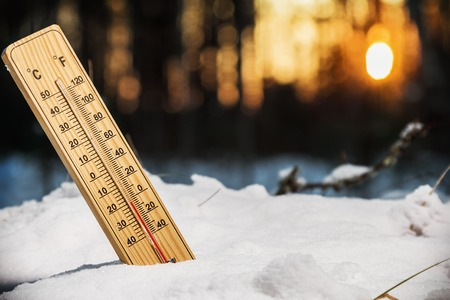 old mercury: thermometer with low temperature in the snowy woods at sunset