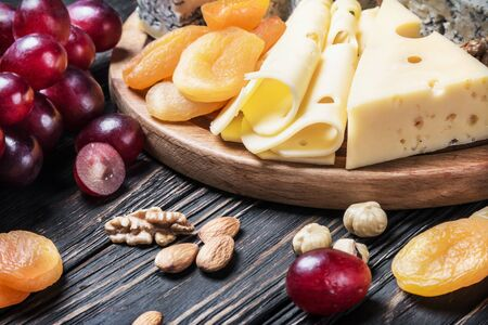 Cheese plate with fruits and nuts on a wooden table Stock Photo