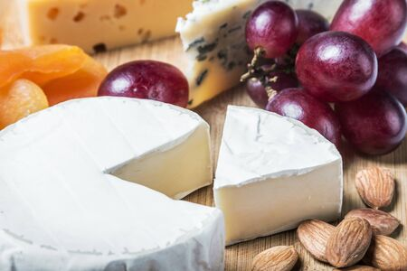 Assorted fresh cheese, fruits and nuts on a wooden table Stock Photo